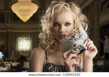 pretty blonde girl with curly hair takes one silver mask, she looks in to the lens and takes the mask with both hands near the chin - stock photo