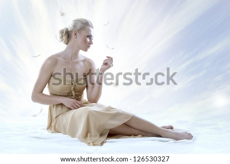 pretty blonde girl with elegant dress sitting on white floor, with a sky as a background, her face is turned at left and she looks in front of her - stock photo