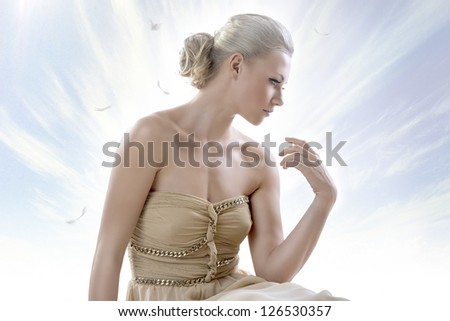 pretty blonde girl with elegant dress sitting on white floor, with a sky as a background , her face is turned is profile at left and her left hand is raised near the shoulder - stock photo