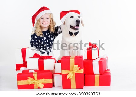 Pretty blonde girl with her friend white labrador dog are wearing christmas hats and sitting with gifts isolates on white in studio - stock photo