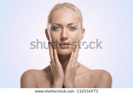 pretty blonde girl with naked shoulders, she touches her face with both hands and looks in to the lens with calm expression - stock photo