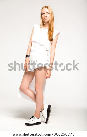 Pretty blonde hipster girl in glasses with red lips posing on white background and have fun.gorgeous autumn outfit,warm white business suit ,toned time,white suit,white shirts,cool sneakers,teenager - stock photo