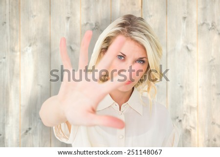 Pretty blonde holding hand up to camera against pale wooden planks - stock photo