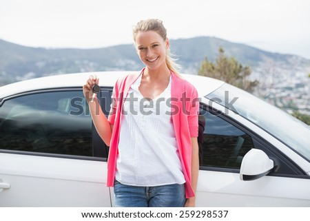 Pretty blonde leaning on the door and holding key of her car - stock photo