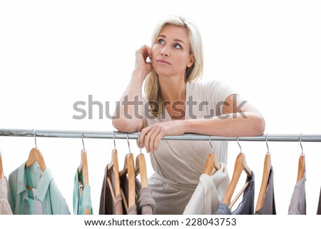 Pretty blonde looking through clothes rail on white background - stock photo