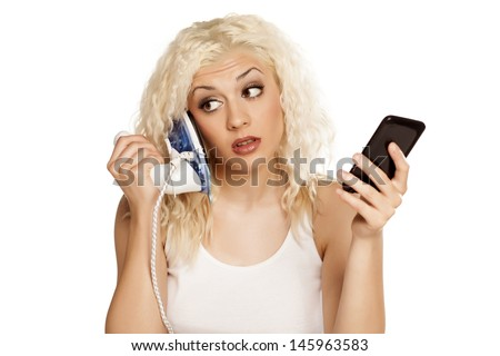 pretty blonde made ??a mistake and answered on the iron, while her phone was ringing - stock photo