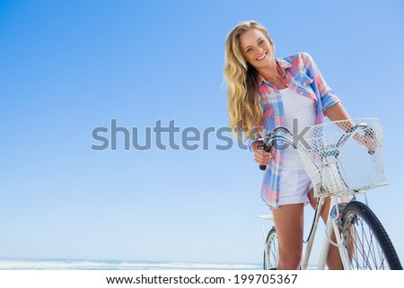 Pretty blonde on a bike ride at the beach smiling at camera on a sunny day - stock photo