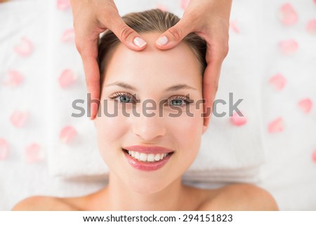 pretty blonde receiving head massage at the spa - stock photo