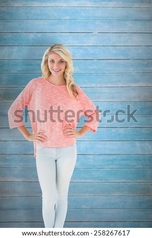 Pretty blonde smiling with hands on hips against wooden planks - stock photo