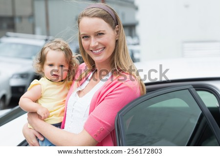 Pretty blonde with her daughter outside her car - stock photo