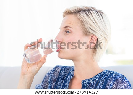 Pretty blonde woman drinking glass of water in the living room - stock photo