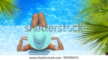 Pretty blonde woman enjoying a swimming pool in Greece - stock photo