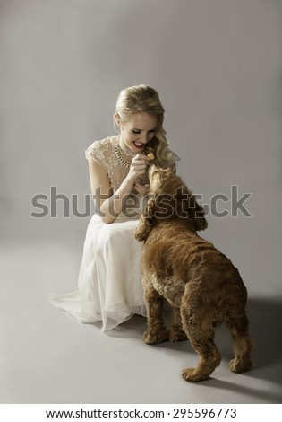 Pretty blonde woman holding a treat for her cute dog - stock photo
