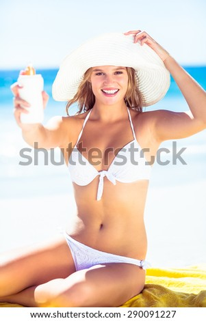 Pretty blonde woman holding sun tan lotion at the beach - stock photo