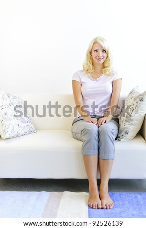 Pretty blonde woman sitting on sofa at home smiling - stock photo