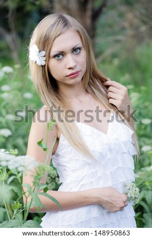 pretty blonde women outdoors in the meadow alone vertical shot - stock photo