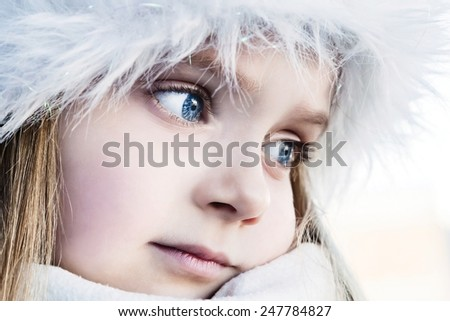 Pretty blue-eyed girl who warms his hands frozen in a cold day - stock photo