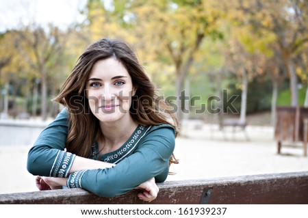 Pretty Blue Eyed Woman Grinning with Fall Trees in Background - stock photo