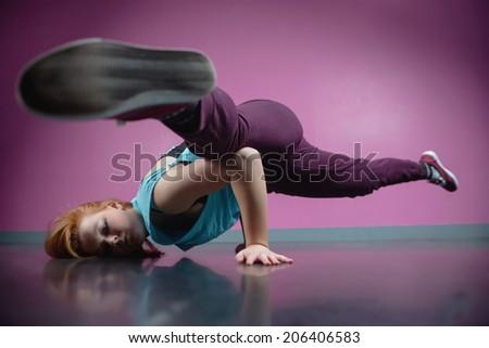 Pretty break dancer busting a move in the dance studio - stock photo