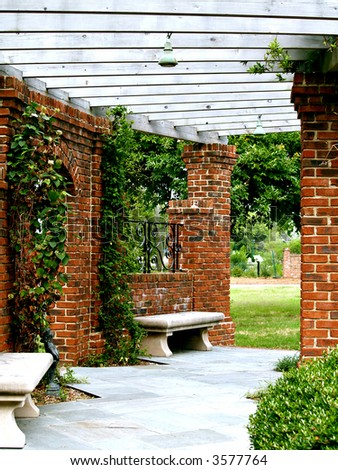 Pretty brick and wood arbor in the garden - stock photo