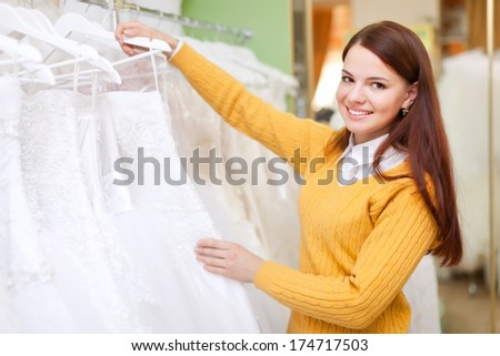 pretty bride chooses  wedding dress in bridal salon - stock photo