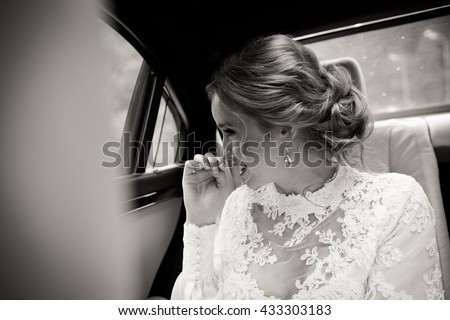 Pretty bride smiles sitting on the back seat in the car - stock photo