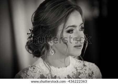 Pretty bride with curly hair cries quietly - stock photo