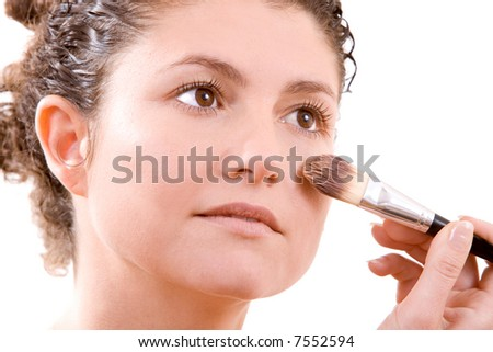 Pretty brunette applying foundation with a big brush - stock photo