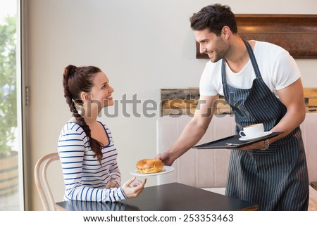 Pretty brunette being served a bagel at the cafe - stock photo