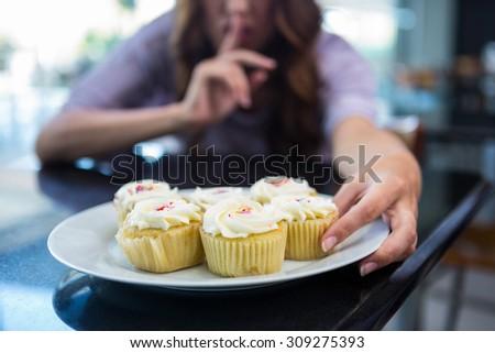 Pretty brunette binging in secret in a coffee shop - stock photo