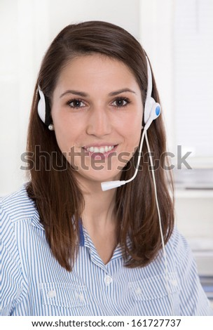 Pretty brunette businesswoman wearing blue blouse with headset - stock photo