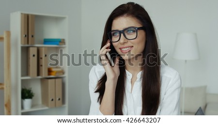 Pretty brunette businesswoman with glasses sitting at desk talking on the phone in office - stock photo