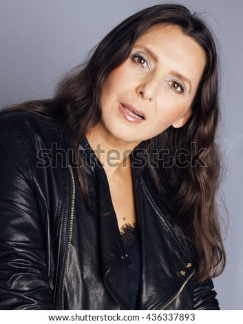 pretty brunette confident stylish real mature woman sitting on chair in studio, sexy  gray background wearing leather jacket - stock photo
