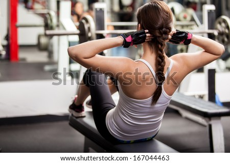 Pretty brunette doing crunches in front of a mirror in a gym - stock photo