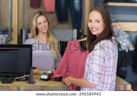 Pretty brunette doing shopping and smiling at camera in clothes store - stock photo