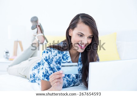 Pretty brunette doing shopping online at home - stock photo