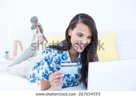 Pretty brunette doing shopping online at home - stock photo