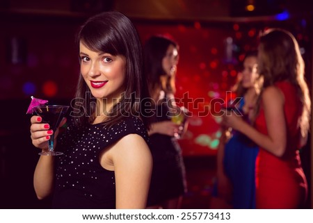 Pretty brunette drinking a cocktail at the nightclub - stock photo