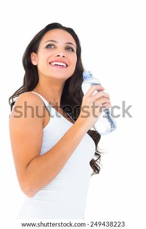 Pretty brunette drinking bottle of water on white background - stock photo