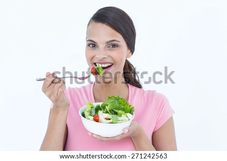 Pretty brunette eating a bowl of salad on white background - stock photo