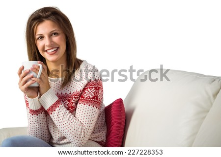 Pretty brunette enjoying a hot drink on the couch at home in the living room - stock photo