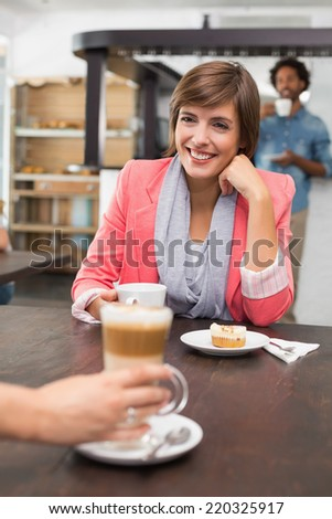 Pretty brunette enjoying her latte with a friend at the coffee shop - stock photo