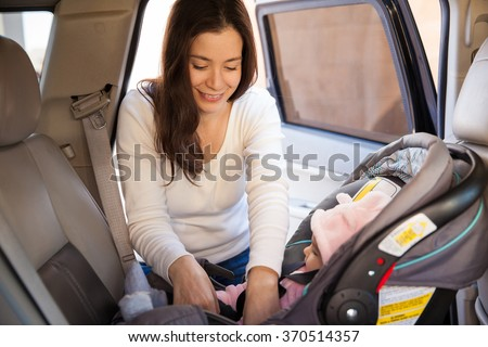 Pretty brunette fastening the seat belt of a child car seat before going for a ride with her baby - stock photo