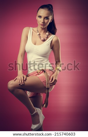 pretty brunette female in active pose wearing sexy stretch top, shorts and suspenders and smiling  - stock photo