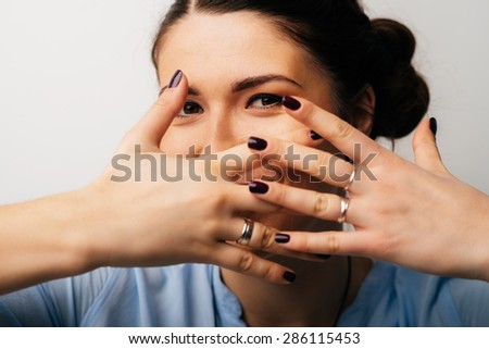Pretty brunette girl covers her face with her hands - stock photo