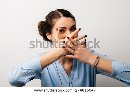 Pretty brunette girl covers her mouth with her hands - stock photo