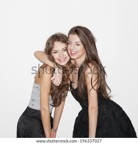 Pretty brunette girl friends having fun. Both looking at camera and smiling (laughing). One hugs another. Festive mood. Inside - stock photo