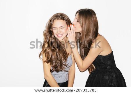 Pretty brunette girl friends having fun. Wearing dresses. One whispering in others ear. Inside - stock photo