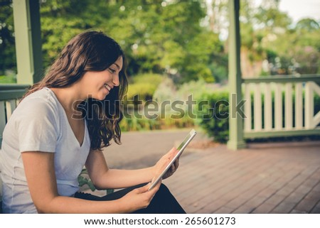 Pretty brunette girl video conferencing on her tablet computer outside in a park. Filtered effects - stock photo
