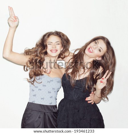 Pretty brunette girls with makeup and pink lips having fun. Jumping, dancing, smiling, showing sign. One looking at camera. Inside  - stock photo